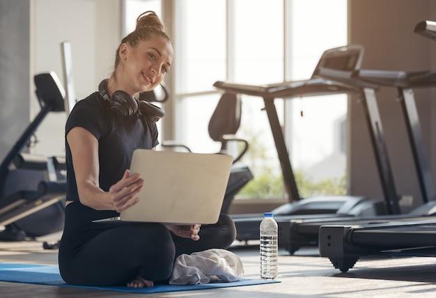 Wysportowana kobieta w stroju sportowym siedzi na podłodze z hantlami i koktajlem proteinowym lub butelką wody i korzysta z laptopa w domu w salonie. pojęcie sportu i rekreacji.