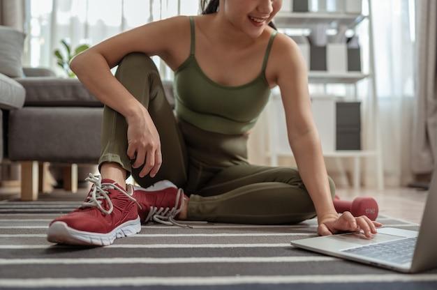 Wysportowana kobieta w stroju sportowym siedzi na podłodze z hantlami i korzysta w domu z laptopa