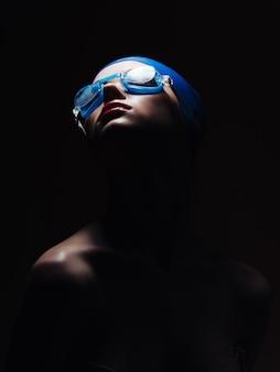 Wysportowana kobieta w studiu treningowym z czepkiem kąpielowym