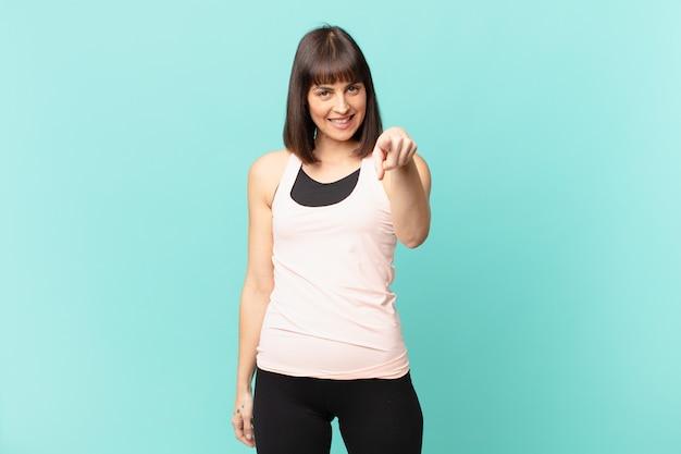 Wysportowana kobieta wskazująca na aparat z zadowolonym, pewnym siebie, przyjaznym uśmiechem, wybierająca ciebie