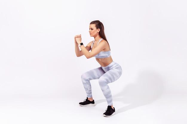 Wysportowana kobieta wykonująca przysiady, ćwiczenia sportowe dolnych partii ciała, utrzymująca równowagę, rozgrzewającą się i trenującą