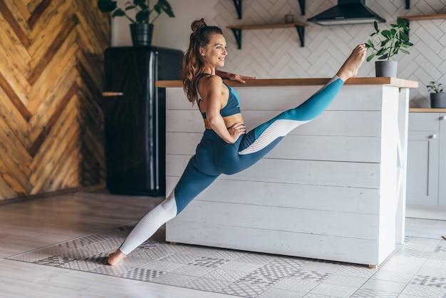 Wysportowana kobieta wykonuje ćwiczenia rozciągające z nogą uniesioną na stole.