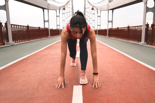 Wysportowana kobieta z bezprzewodowymi słuchawkami rozciągająca się przed biegiem podczas przebywania na moście na świeżym powietrzu