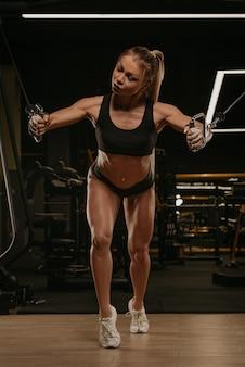 Wysportowana kobieta z długimi blond włosami ćwiczy klatkę piersiową na kablówce w siłowni. dziewczyna ćwiczy mięśnie piersiowe.