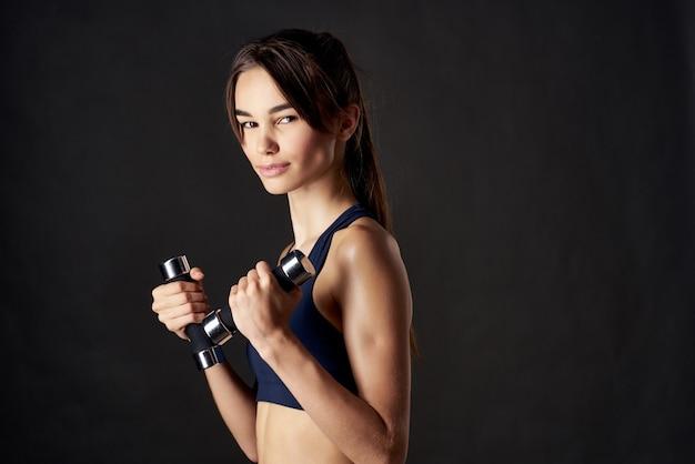 Wysportowana kobieta z hantlami w ręku z siłownią w studio ćwiczeń