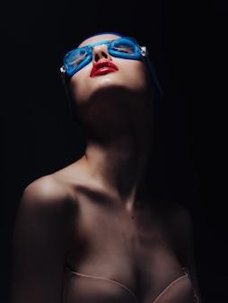 Wysportowana kobieta z nagimi ramionami i czerwonymi ustami studio treningu