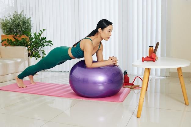 Wysportowana młoda azjatka balansująca na piłce fitness podczas treningu abs na tablecie