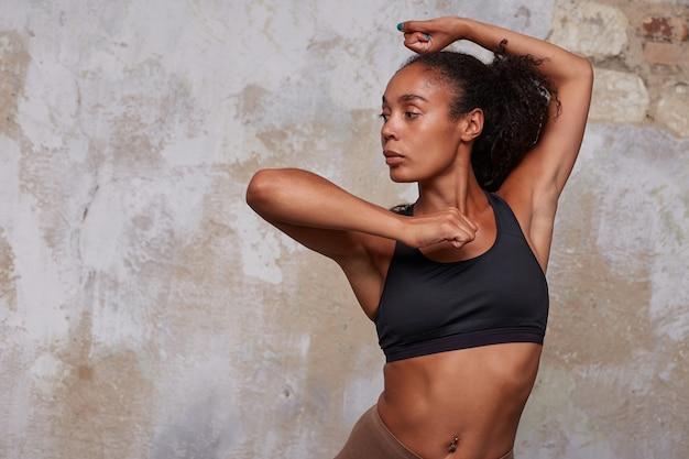 Wysportowana, młoda, ciemnoskóra, kręcona kobieta w czarnej sportowej bluzce, wykonująca element taneczny i spoglądająca na bok z poważną miną, stojąca nad wnętrzem loftu