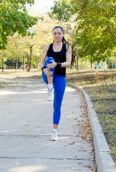 Wysportowana młoda dama ćwiczy w parku, balansując na jednej nodze, zginając i rozciągając drugie kolano zgodnie z koncepcją zdrowia i sprawności