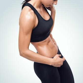 Wysportowana młoda kobieta ma przerwę w siłowni, pokazując swoje dobrze wytrenowane ciało.
