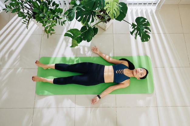 Wysportowana młoda kobieta odpoczywa w pozie shavasana po ćwiczeniu jogi w domu, widok z góry