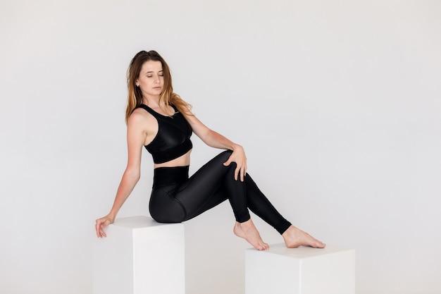 Wysportowana młoda kobieta robi praktykę jogi na białym tle koncepcja zdrowego życia...