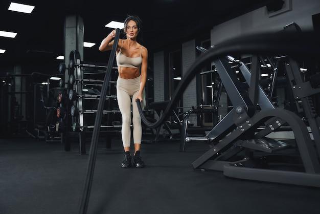 Wysportowana młoda kobieta robi trening liny bojowej