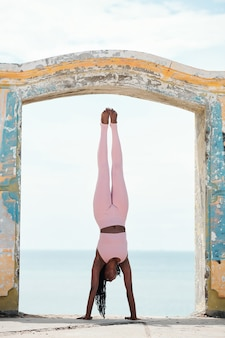 Wysportowana młoda kobieta w jasnoróżowych legginsach i sportowym staniku robi stanie na rękach w starym łuku na wybrzeżu