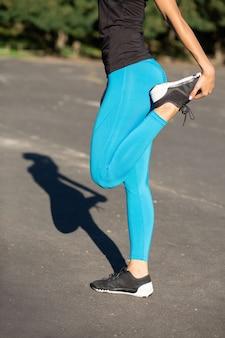 Wysportowana młoda kobieta w stroju sportowym, rozciągająca się przed treningiem na stadionie