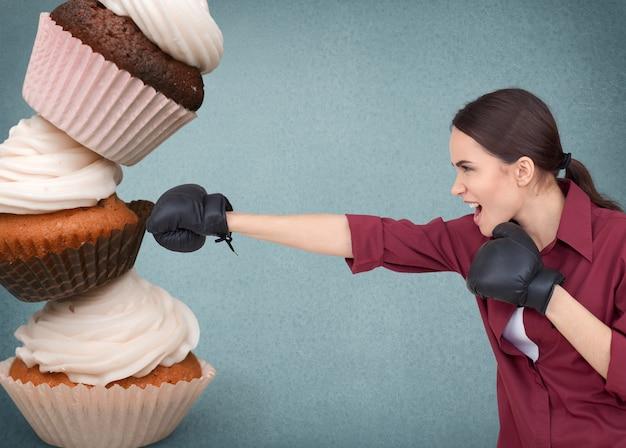 Wysportowana młoda kobieta walcząca z fast foodami