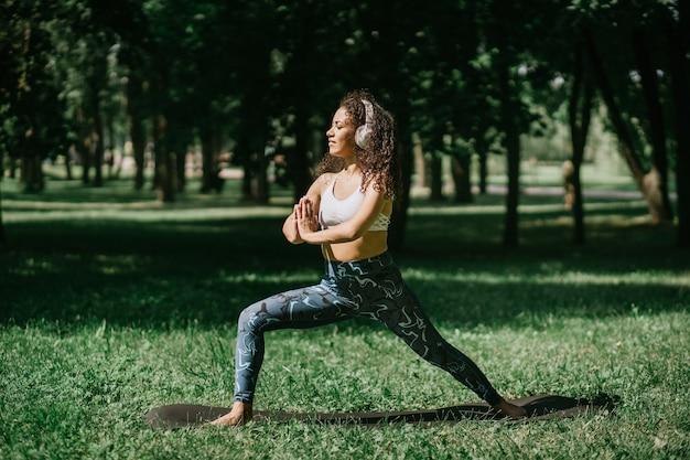 Wysportowana młoda kobieta wykonująca ćwiczenia stojąc na trawie