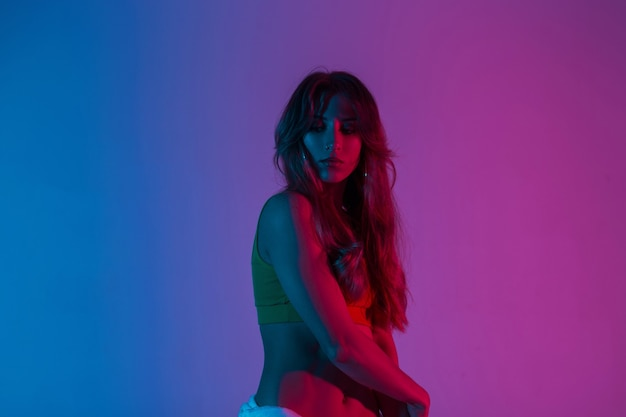 Wysportowana młoda kobieta z długimi włosami w modnej górze pozuje w pokoju na niebieskim kolorowym tle. sexy dziewczyna modelka w modnym stroju stoi w studio z jasnym neonowym różowym światłem.