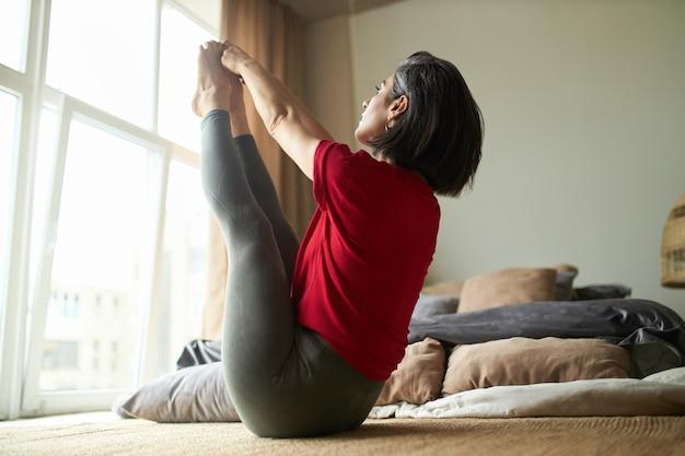 Wysportowana młoda kobieta z silnym dopasowanym ciałem praktykuje jogę w sypialni, siedząc w górę, twarzą do intensywnej pozycji rozciągania
