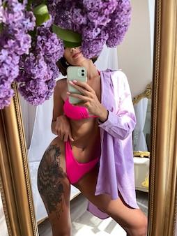 Wysportowana, opalona kobieta o idealnym ciele robi zdjęcie selfie na telefonie w lustrze w domu