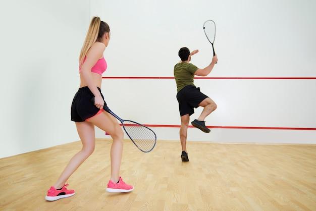 Wysportowana para grająca razem w squasha