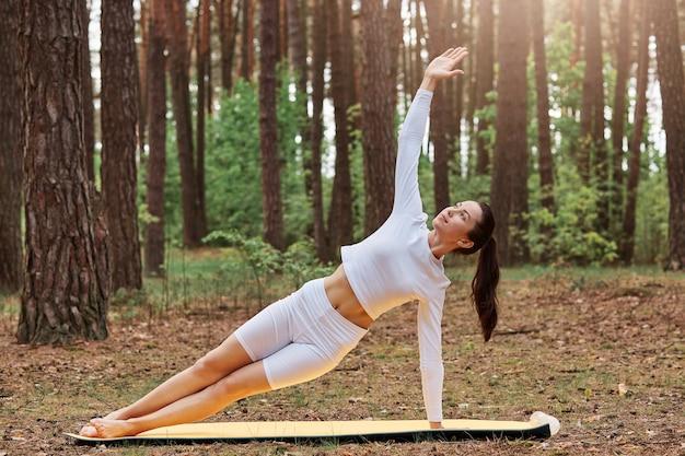 Wysportowana piękna dziewczyna w białej modnej odzieży sportowej, szortach i topie, ćwicząca jogę, wykonująca pozę deski bocznej z podniesionym ramieniem, trening mięśni i siłę