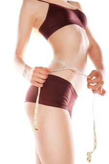 Wysportowana szczupła kobieta mierząca talię za pomocą taśmy mierniczej po diecie izolowanej na białym tle
