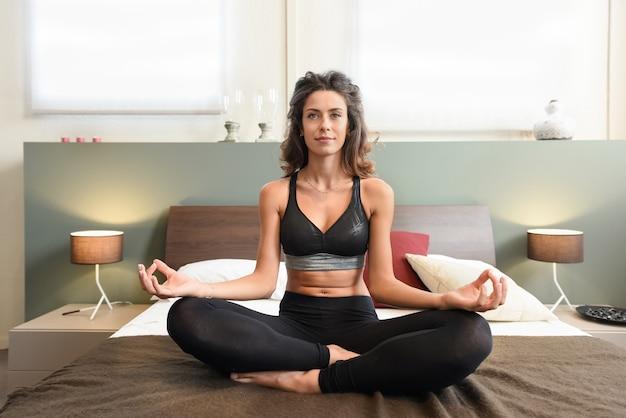 Wysportowana, zdrowa kobieta medytująca w sypialni siedząca na łóżku w pozie lotosu z pogodnym uśmiechem