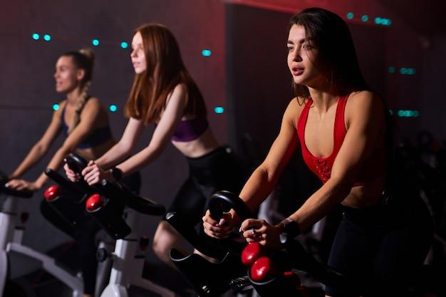 Wysportowane kobiety ćwiczące na rowerze stacjonarnym na siłowni, intensywny trening cardio na siłowni. koncepcja sportu i zdrowego stylu życia