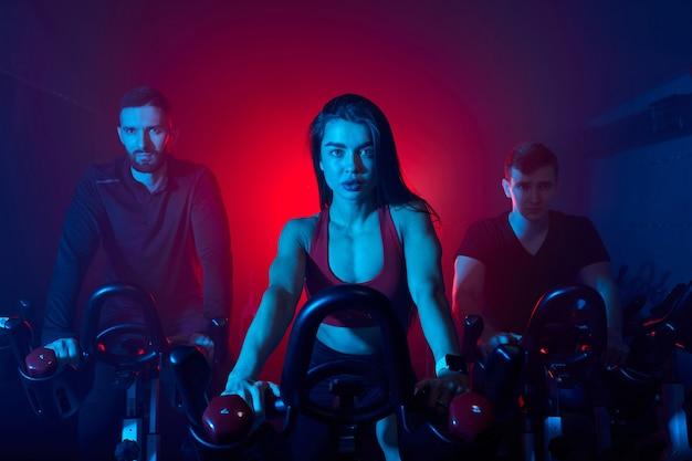 Wysportowani ludzie ćwiczący i ćwiczący na siłowni, rower maszynowy, noszący dres. trening, zdrowie, wellness w fitness