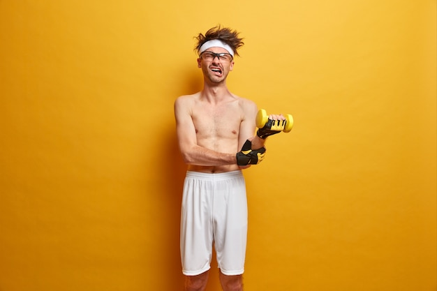 Wysportowany facet fitness podnosi ciężkie hantle, ćwiczy na ramiona, ma dużo energii, odczuwa ból, wykazuje motywację sportową, nosi szorty i sportowe rękawiczki. koncepcja ludzie, zdrowie, pielęgnacja ciała i fitness w domu
