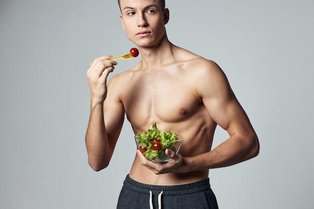 Wysportowany facet z umięśnionym torsem płyta sałatka warzywa zdrowe jedzenie energia food