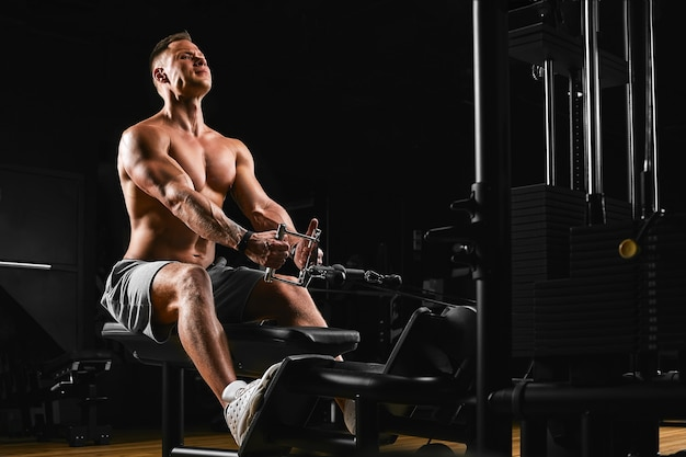 Wysportowany i umięśniony mężczyzna trenuje mięśnie klatki piersiowej na symulatorze klocków w siłowni