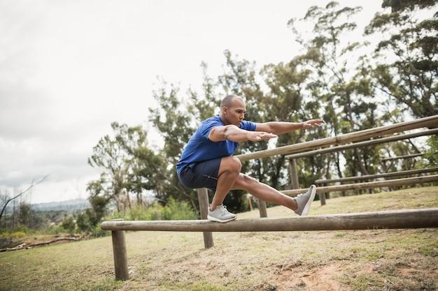Wysportowany mężczyzna balansujący na płotkach podczas treningu na torze przeszkód na obozie treningowym