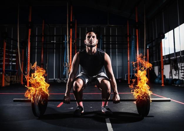 Wysportowany mężczyzna ćwiczy na siłowni z ognistą sztangą