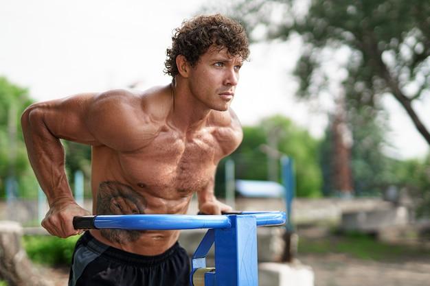 Wysportowany mężczyzna ćwiczy ręce na pompkach poziomych drążkach trenuje triceps i biceps robi pompki przystojny...