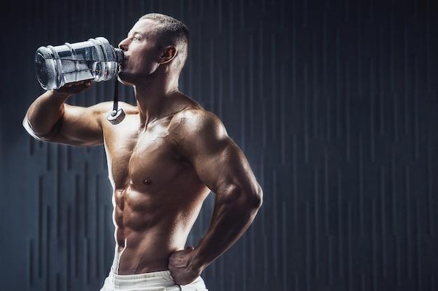 Wysportowany mężczyzna na treningu w siłowni z shakerem na ciemnym tle