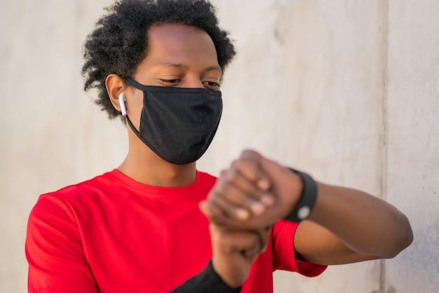 Wysportowany mężczyzna nosi maskę na twarz i sprawdza czas na swoim inteligentnym zegarku podczas ćwiczeń na świeżym powietrzu. nowy normalny styl życia. koncepcja sportu i zdrowego stylu życia.