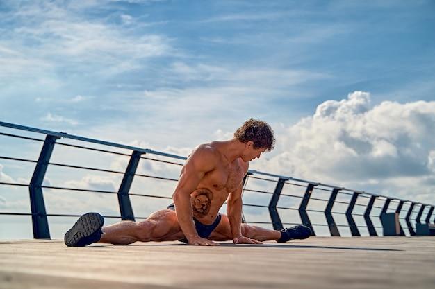 Wysportowany mężczyzna o pięknych mięśniach siedzi na sznurku podczas letniego treningu na molo nad morzem