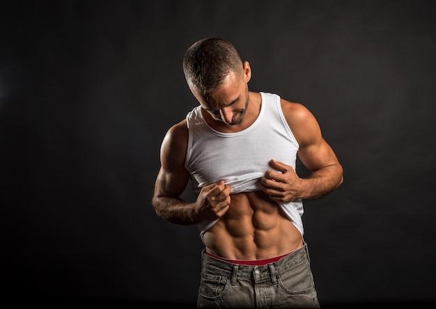 Wysportowany mężczyzna podnoszący koszulę, by pokazać swój abs.