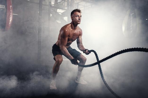 Wysportowany mężczyzna robi ćwiczenia crossfit z liną w zadymionej siłowni