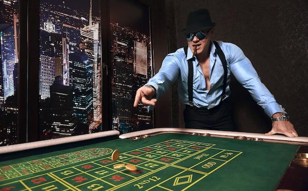 Wysportowany mężczyzna ubrany w garnitur z cygarem gra w kasynie