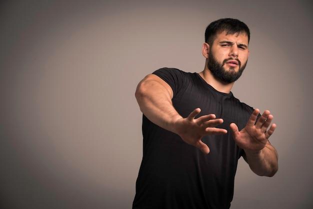 Wysportowany mężczyzna w czarnej koszuli broni się i unika walki.