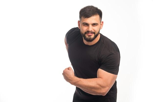 Wysportowany mężczyzna w czarnej koszuli pokazuje jego bicepsy.