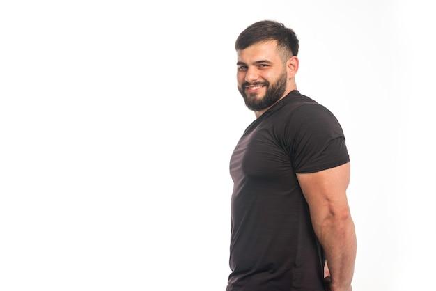 Wysportowany mężczyzna w czarnej koszuli pokazuje jego triceps