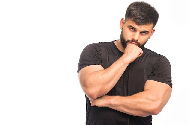 Wysportowany mężczyzna w czarnej koszuli pokazuje pięści i przyjmuje myślącą pozycję