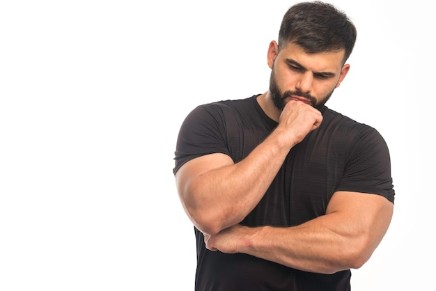 Wysportowany mężczyzna w czarnej koszuli pokazuje pięści i przyjmuje myślącą pozycję.