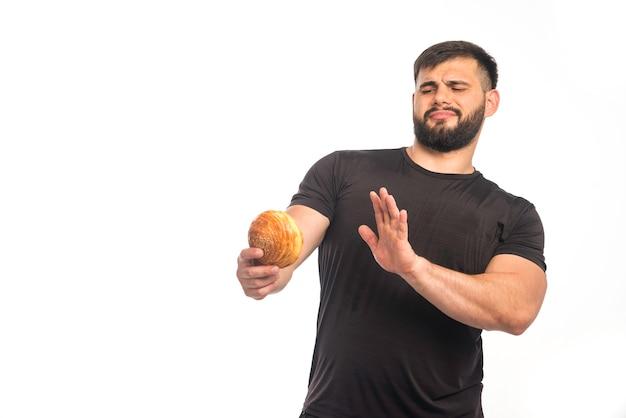 Wysportowany mężczyzna w czarnej koszuli trzyma pączka i odmawia.