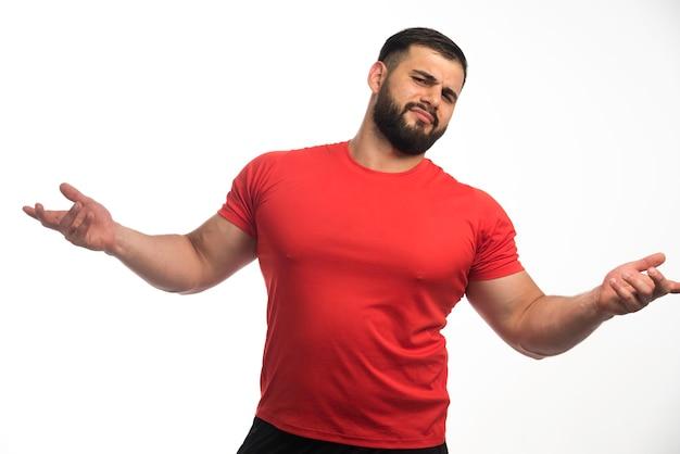 Wysportowany mężczyzna w czerwonej koszuli wygląda agresywnie.