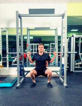 Wysportowany mężczyzna w sportowej podnoszenia sztangi patrząc skoncentrowany, poćwiczyć na siłowni